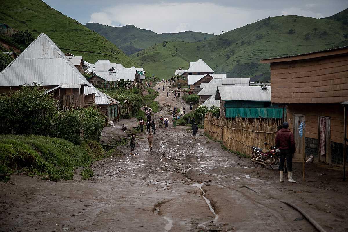Plano general de la calle principal de Numbi, toda embarrada, que cruza casas de madera y paja con tejados de hojalata.