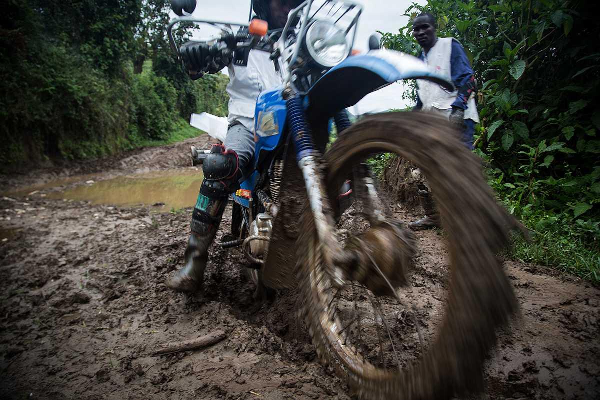 Primer plano de la rueda delantera de una moto que avanza hacia la cámara sobre el barro del camino.