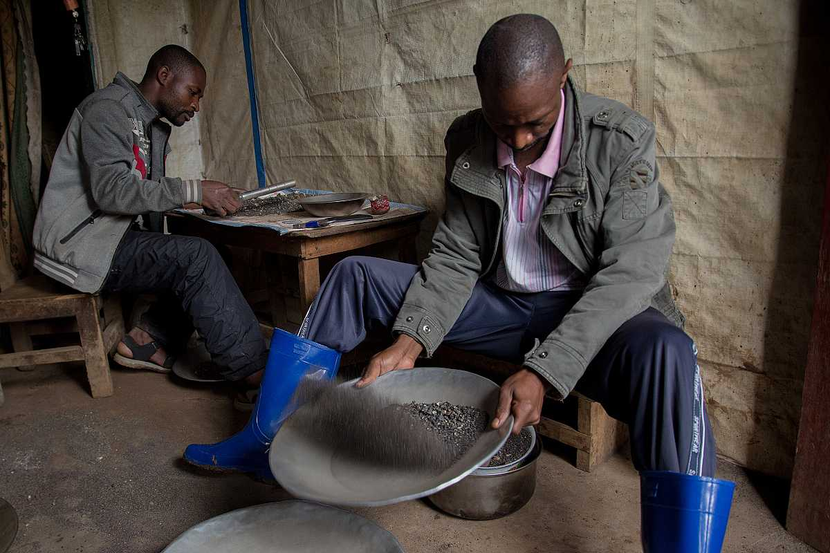 Dos trabajadores de la mina de coltán limpiando la tierra extraída para separar el mineral.