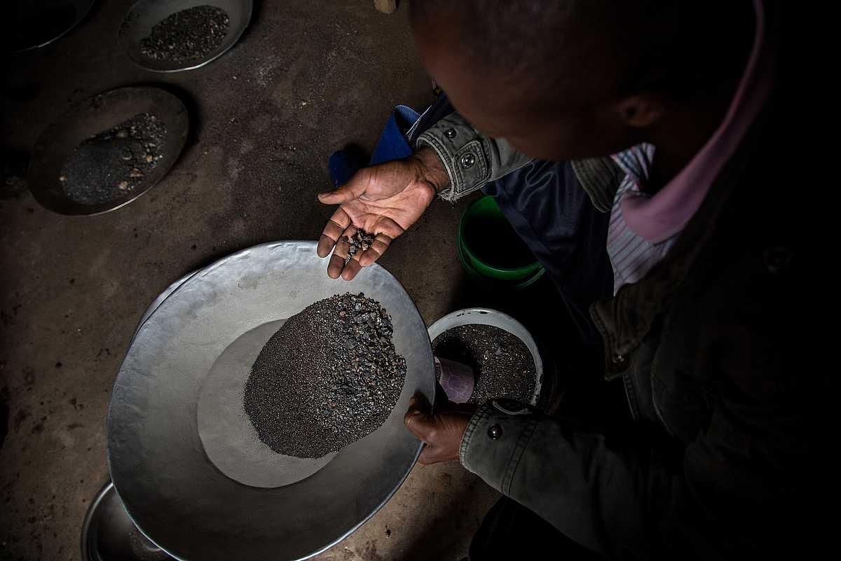 Plano cenital de un trabajador de la mina de cotán enseñando unas piedras de mineral recogidas de las bandejas de separación.