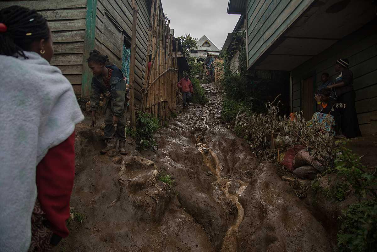 Un gran río de barro sirve como calle de separación a unas hileras de casas en Numbi.