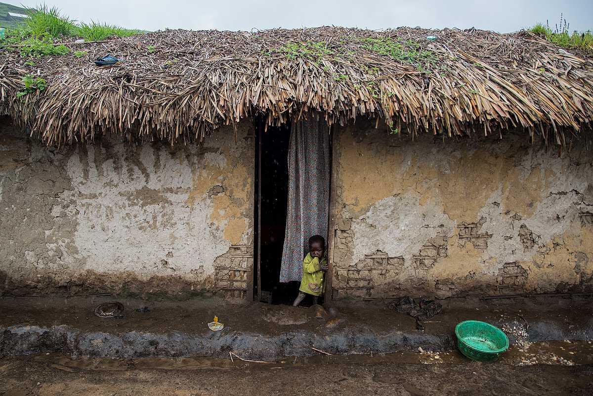 Un niño pequeño en la puerta de su casa en Numbi.