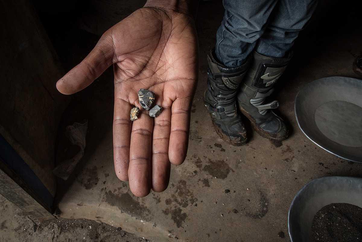 Primer plano de la mano de un minero mostrando piedras de coltán.