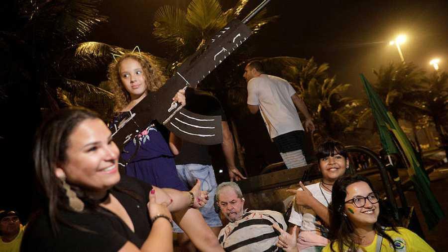 Partidarios de Jair Bolsonaro posan con un arma de cartón y un muñeco que representa al expresidente Lula preso