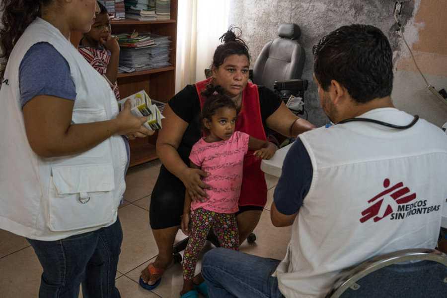 Piedad sostiene a su hija durante una consulta con personal sanitario de MSF