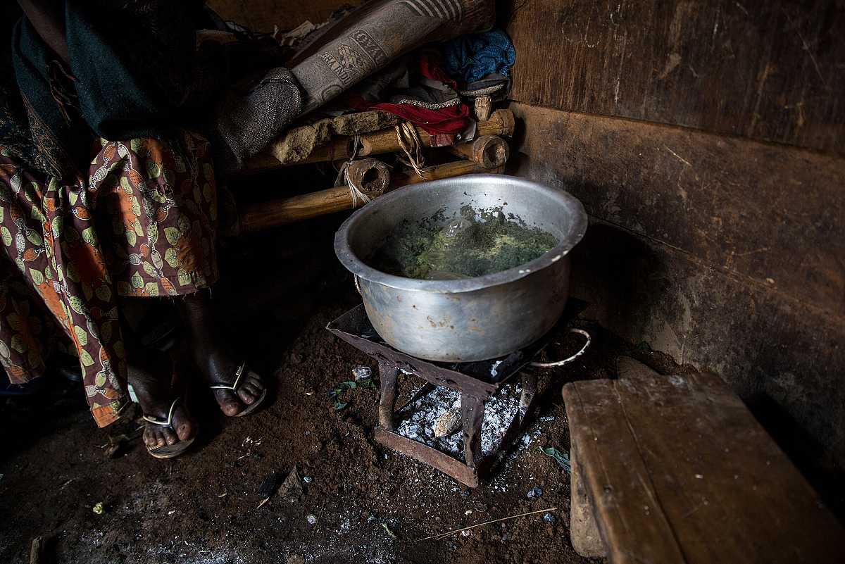 Un primer plano de una cacerola sobre una pequeña lumbre, donde se cocina la mandioca.