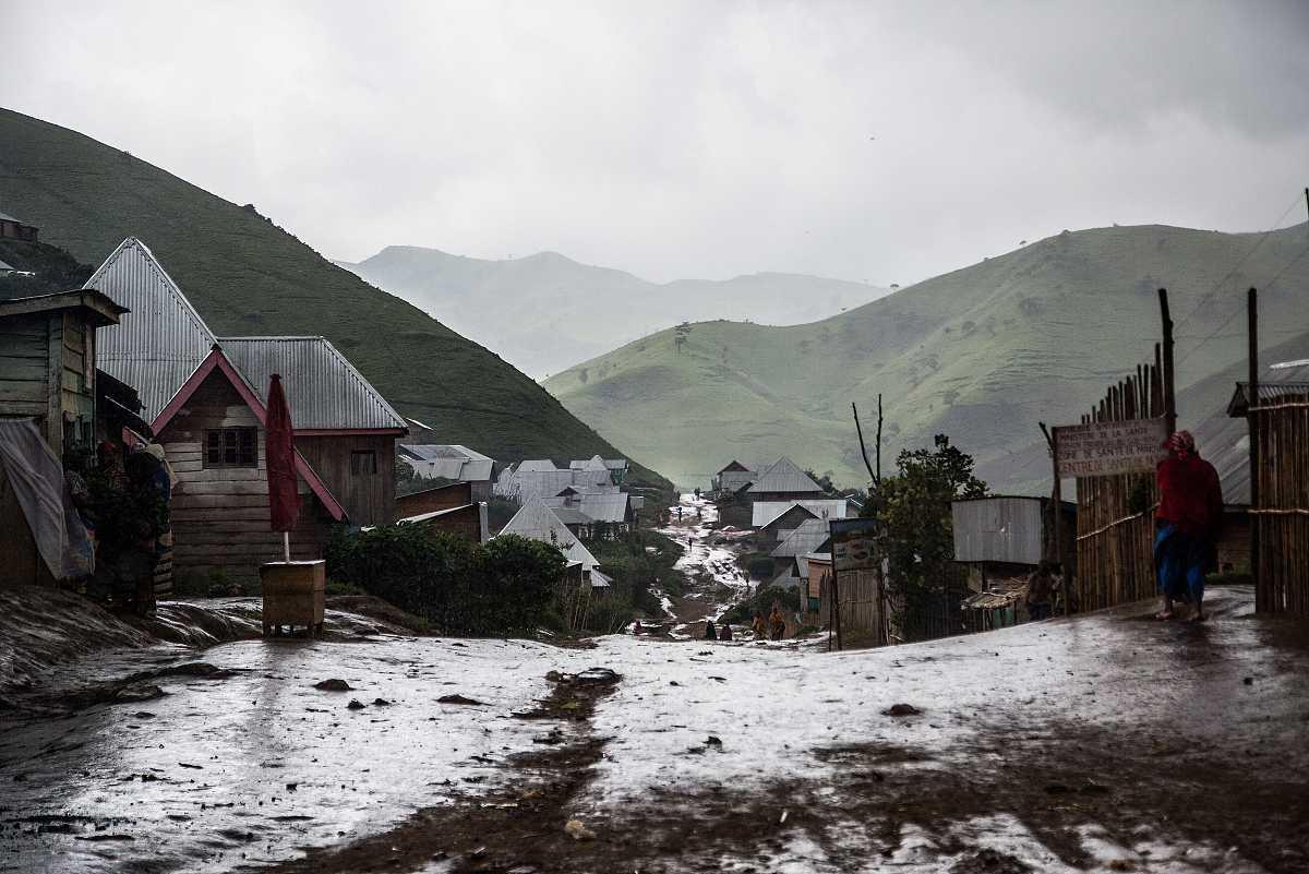 Imagen de Numbi lloviendo, vista desde lo alto de su calle principal. Varias figuras caminan por la brillante y mojada pista de tierra.