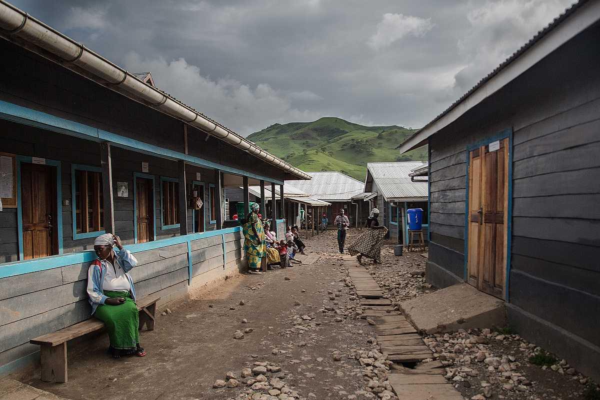 Varias personas esperan en la parte exterior del hospital de Numbi, bajo un porche.
