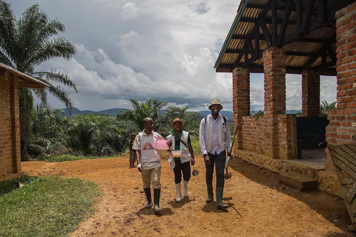 Tres miembros de MSF avanzan por las calles de Lulingu, con Severin Ndo situado a la derecha del grupo.