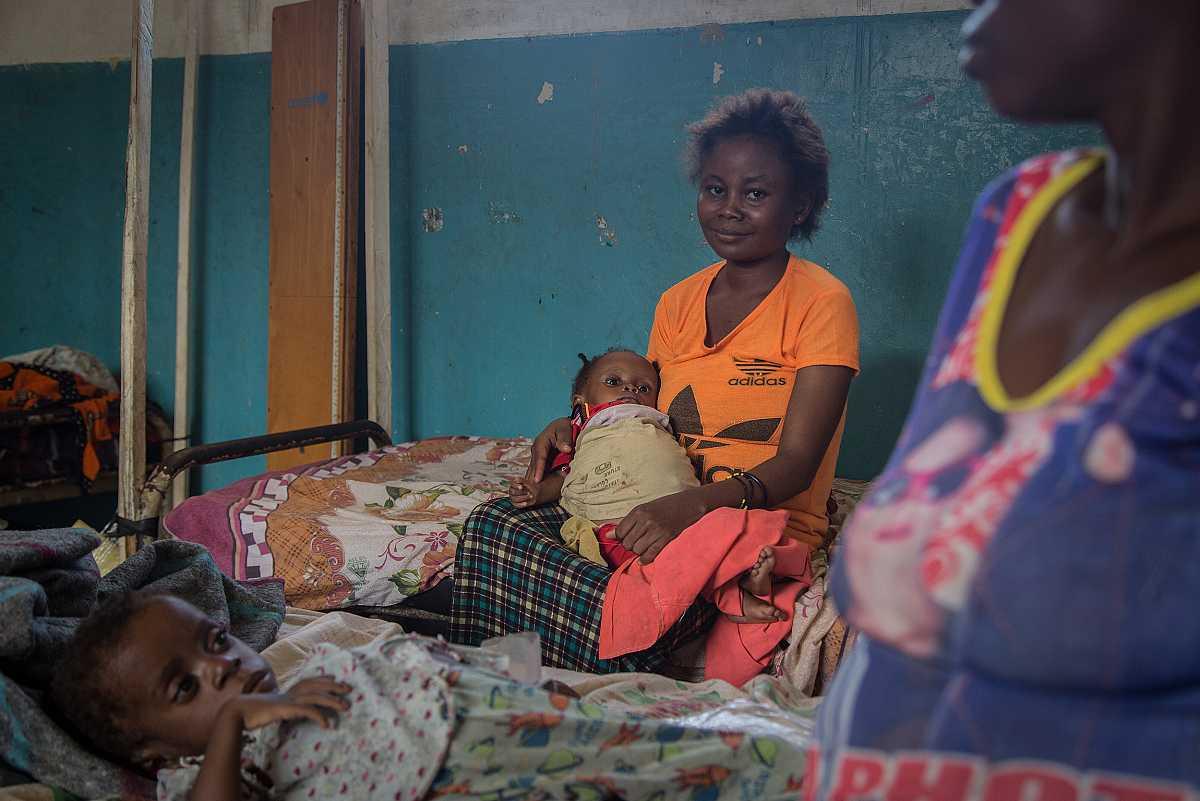 Una mujer con una camiseta naranja espera sentada en la cama del hospital de Lulingu con su hijo en brazos.