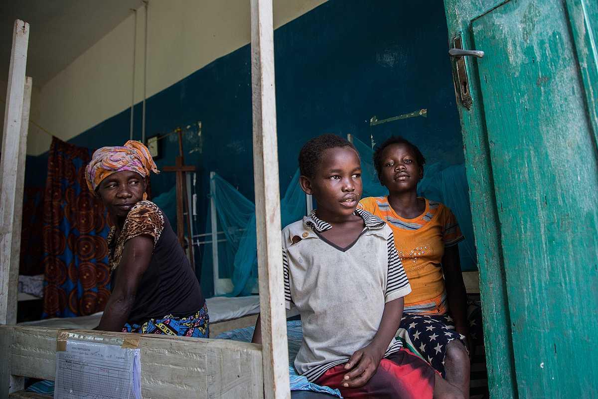 Séraphine, junto a su madre y hermana, permanece sentado en una de las camas del hospital de Lulingu.