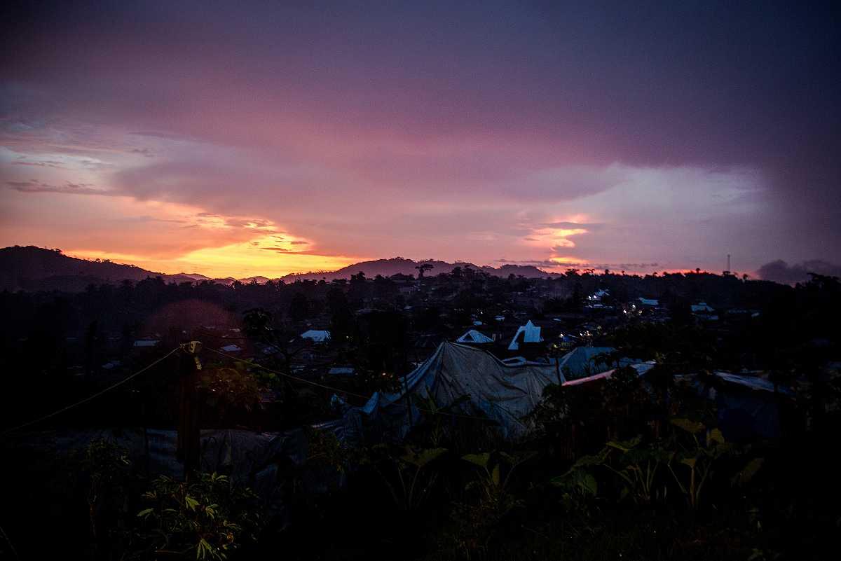 Atardecer sobre la población de Lulingu. El sol se pone tras los montes cercanos mientras se encienden algunas farolas entre casas y tiendas de campaña.