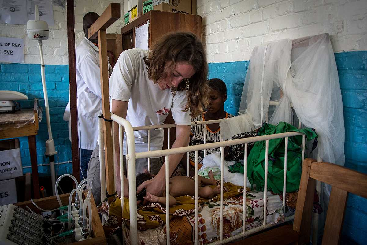 Una cooperante de MSF atiende a un bebé que permanece en una cuna, ante la atenta mirada de su madre.