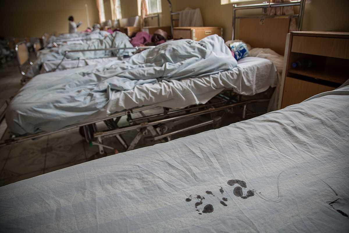 Una larga hilera de camas con pacientes del hospital Panzi y en primer término una vacía, recién desocupada.