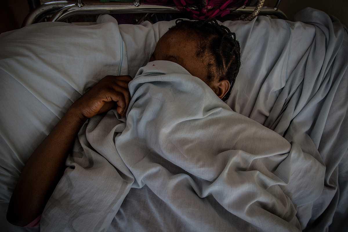 Una mujer se tapa la cara con las sábanas de su cama en el hospital.