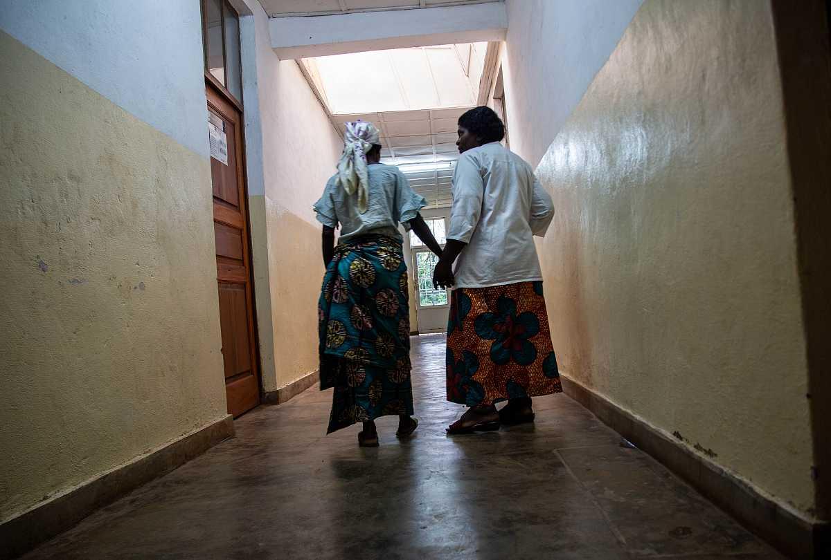 Esther consuela a una mujer que llora, Mapanzi, que fue violada en su propia casa