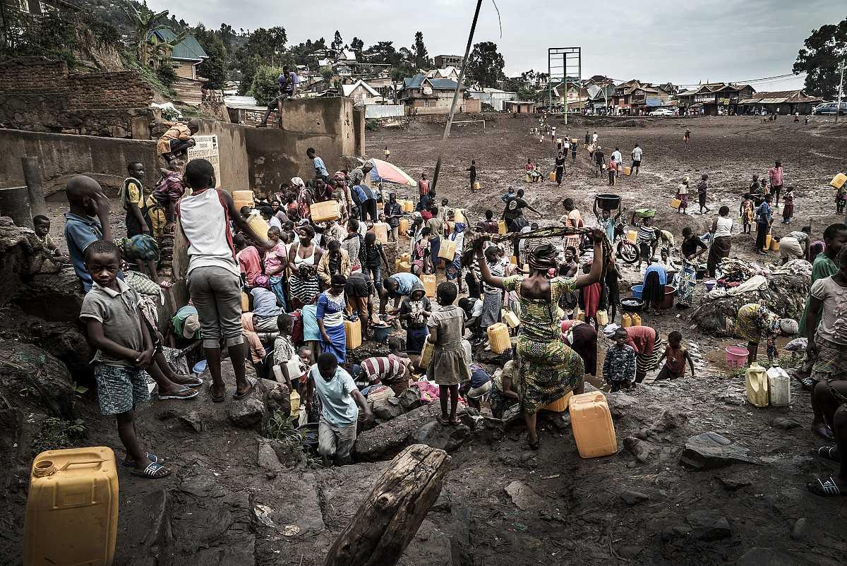 Una multitud de personas esperan su turno para llenar garrafas con agua potable en una fuente pública.