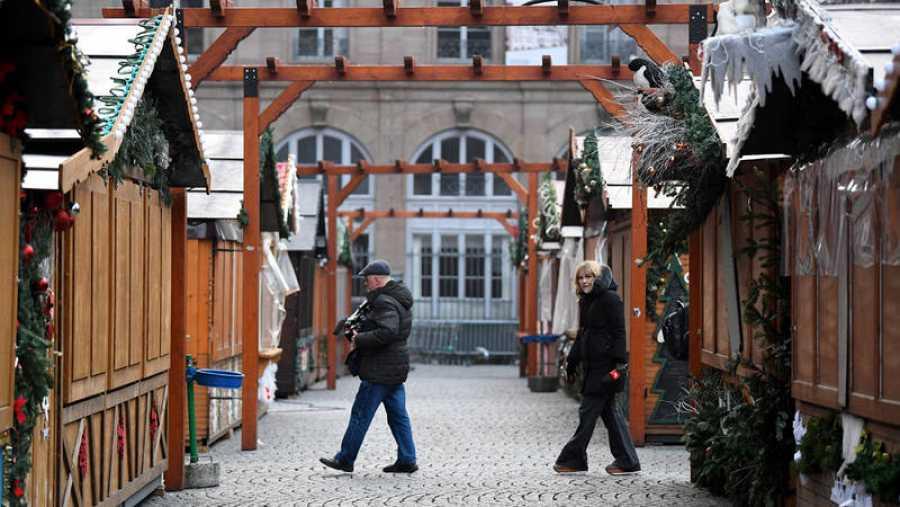 Dos reporteros caminan entre las casetas cerradas del mercadillo navideño objeto de un atentado perpetrado ayer, en Estrasburgo (Francia)