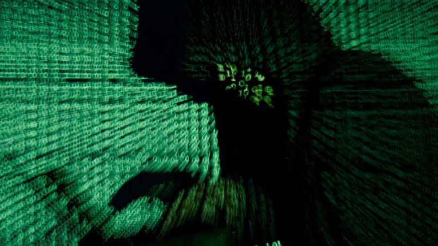 Un hombre sostiene una computadora portátil mientras se proyecta sobre él un código cibernético.