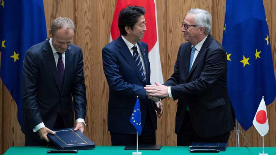 El primer ministro japonés, Shinzo Abe (c), estrecha la mano del presidente de la Comisión Europea, Jean-Claude Junker (d)