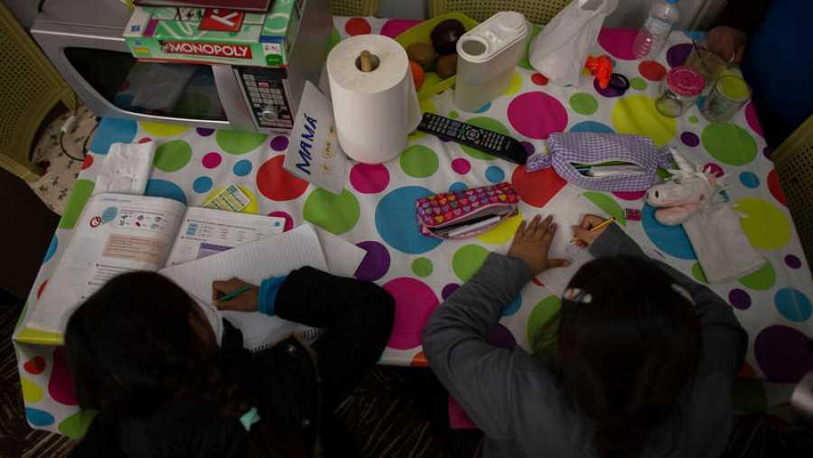 Manos de niños estudiando en una mesa de casa.