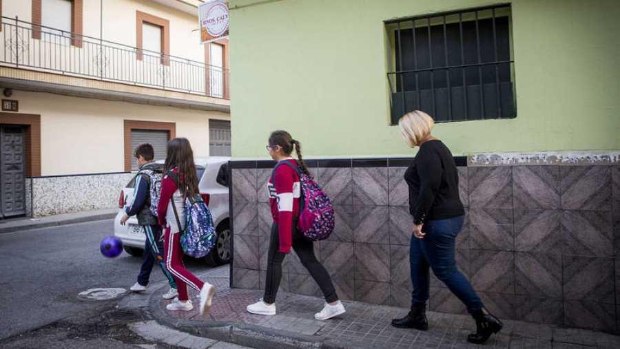 Una madre acompaña a sus tres hijos al colegio en Sevilla.