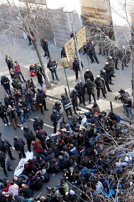 Vista de un grupo de manifestantes sentados en la calzada frente a la Fiscalía General de Cataluña