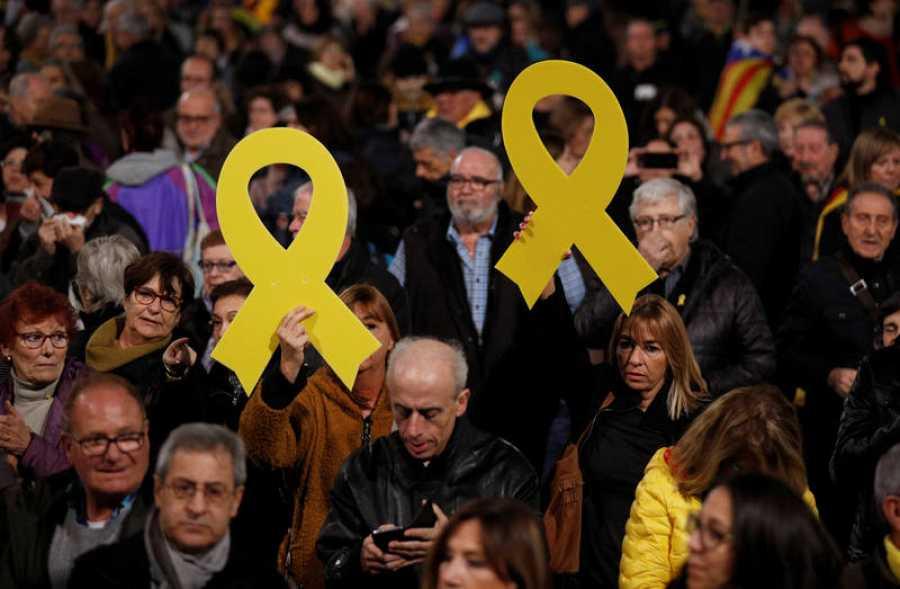 Manifestantes muestran lazos amarillos en la protesta contra el juicio del 'procés' convocada en la Plaza de Catalunya de Barcelona.