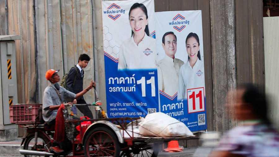 Un hombre monta un vehículo para recolectar basura reciclable frente a un cartel de la campaña electoral con un retrato del primer ministro tailandés y líder de la junta Prayut Chan-o-cha