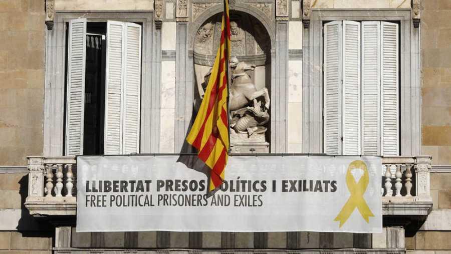 Vista del cartel reclamando la libertad de los líderes independentistas presos y un lazo amarillo en la fachada del Palau de la Generalitat