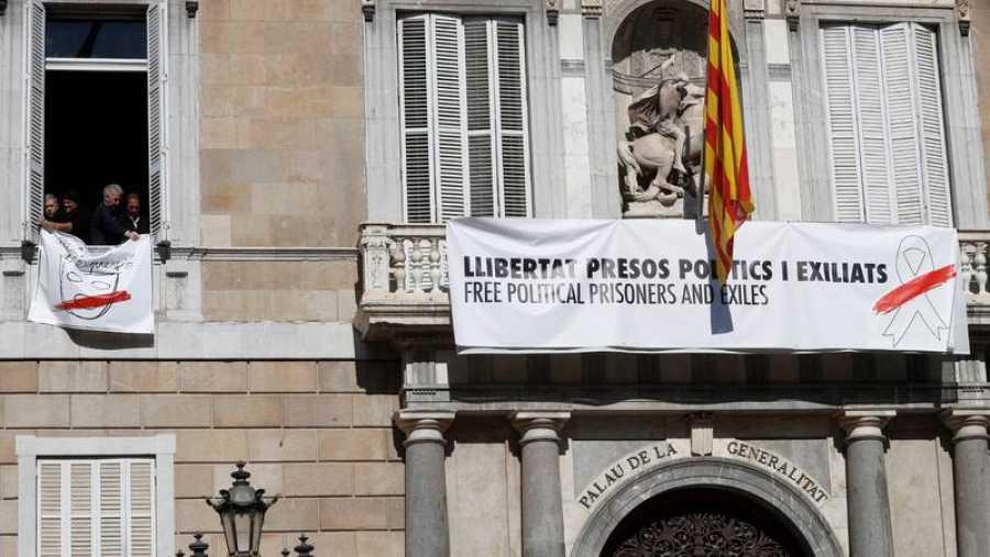 Pancarta con un lazo blanco sobre la anterior con un lazo amarillo en el Palau de la Generalitat