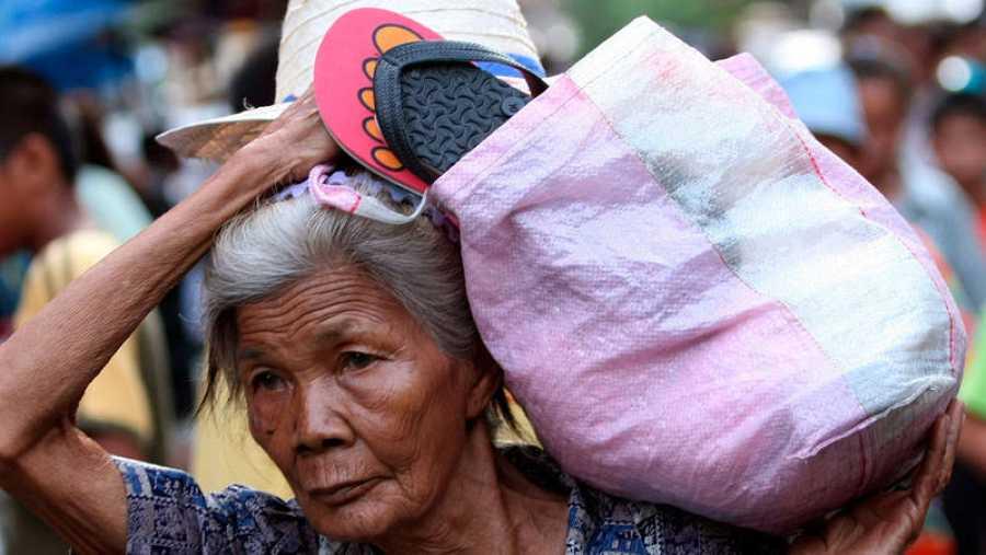 Una anciana tailandesa con una cesta en el hombro