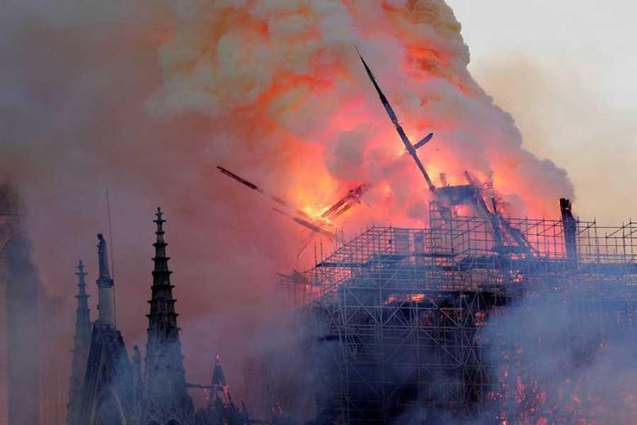 La aguja central de la catedral de Notre Dame cae durante un incendio este lunes en la capital francesa.