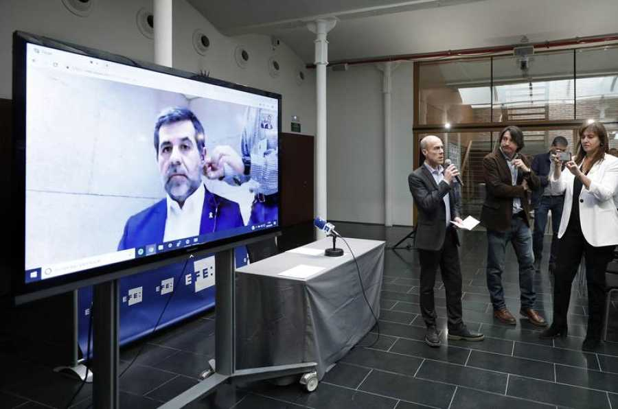 Periodistas siguen a través de un monitor la entrevista electoral al candidato de JxCat y expresidente de la ANC Jordi Sànchez desde prisión.