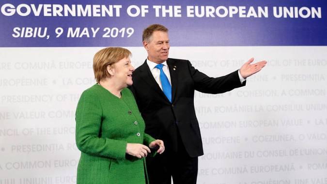 La canciller alemana Angela Merkel saluda al presidente rumano al llegar a la cumbre de Sibiu
