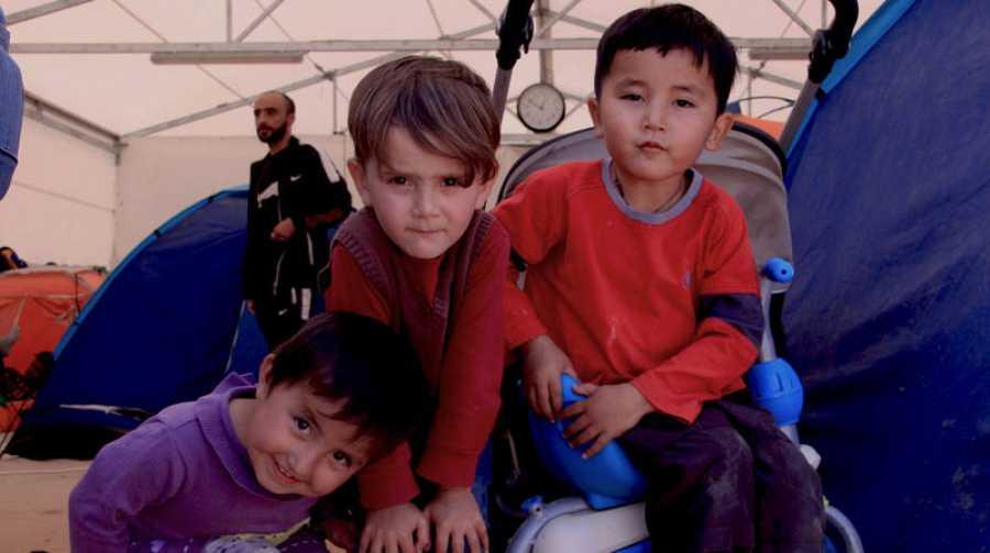 Niños afganos en la entrada del campo de refugiados de Malakasa