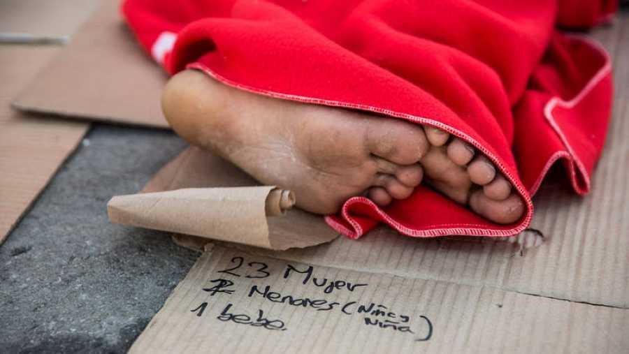 Un hombre duerme en el puerto de Algeciras después de ser rescatado por Salvamento Marítimo en el Estrecho de Gibraltar. Debajo de sus pies hay escrito un listado de las personas que Salvamento Marítimo salvó de una patera. © Olmo Calvo.