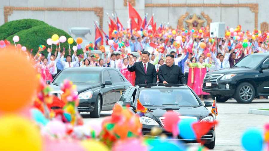 El líder norcoreano Kim Jong Un (R) y el presidente chino Xi Jinping saludaron a la multitud a su llegada a Pyongyang