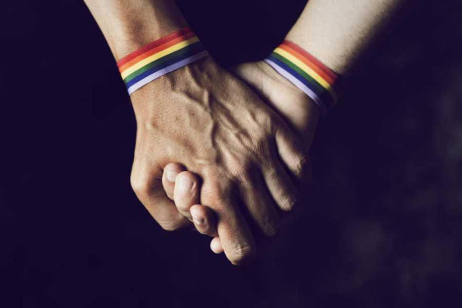 Las manos de dos personas agarradas y con pulseras de arcoíris en representación de la bandera LGTBI.