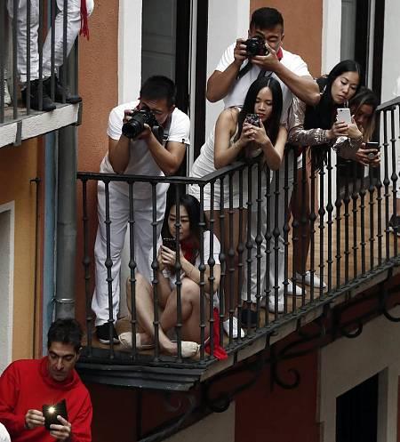 Un grupo de turistas orientales toman fotografías del encierro