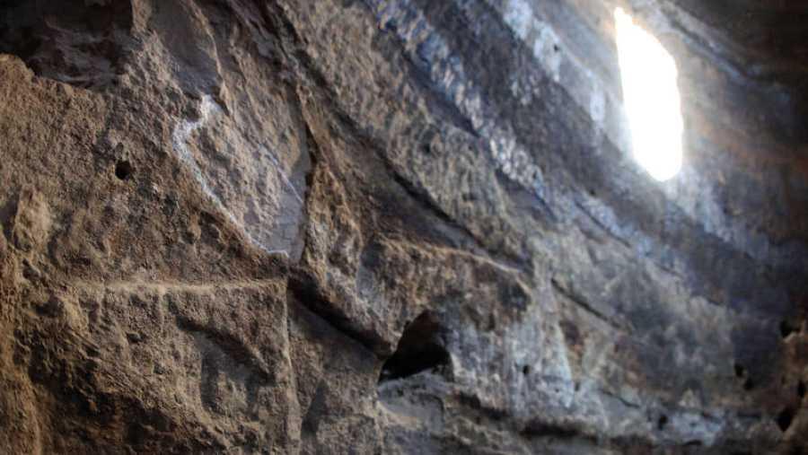 La entrada del haz de luz en Risco Caído durante el solsticio de verano y la pared de grabados que va iluminando a su paso.