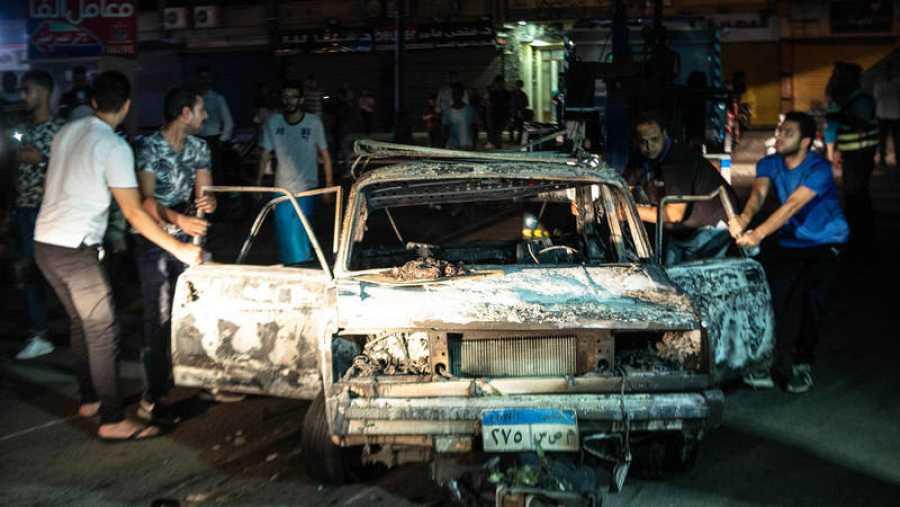 Varias personas rodean uno de los coches quemados en una explosión frente a un  hospital de El Cairo