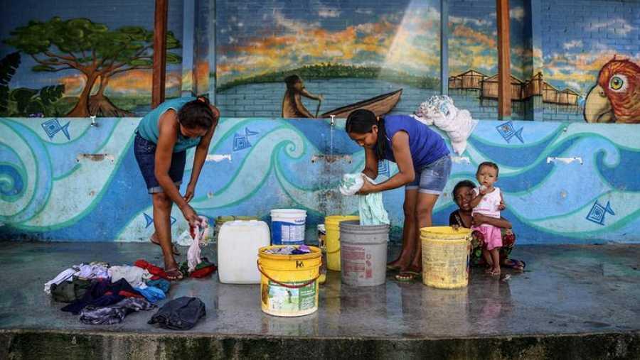 Las mujeres lavan su ropa en el refugio de Pintolandia, en Boa Vista. El suministro de agua y el saneamiento se encuentran en malas condiciones en el refugio.