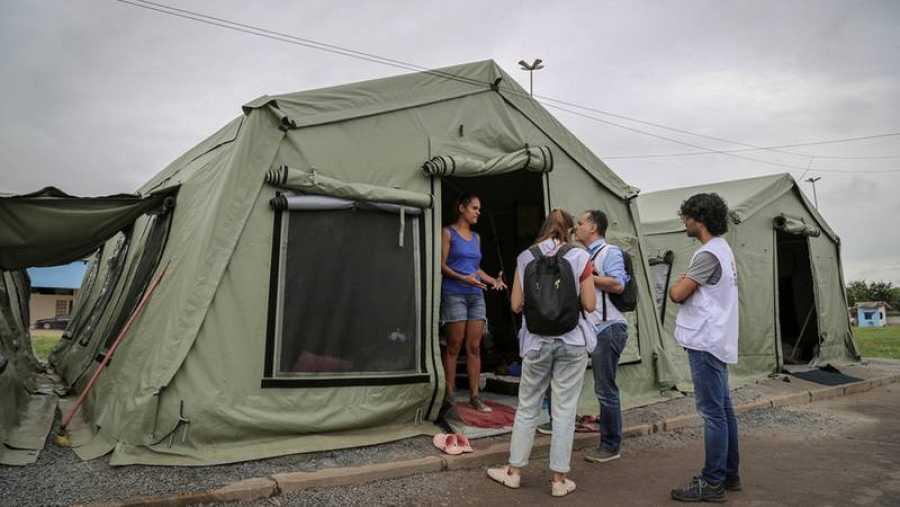 Un equipo de MSF habla con Milagros Linares. Ella vive con sus dos hijos y su esposo en un área detrás de la estación de autobuses de Boa Vista.