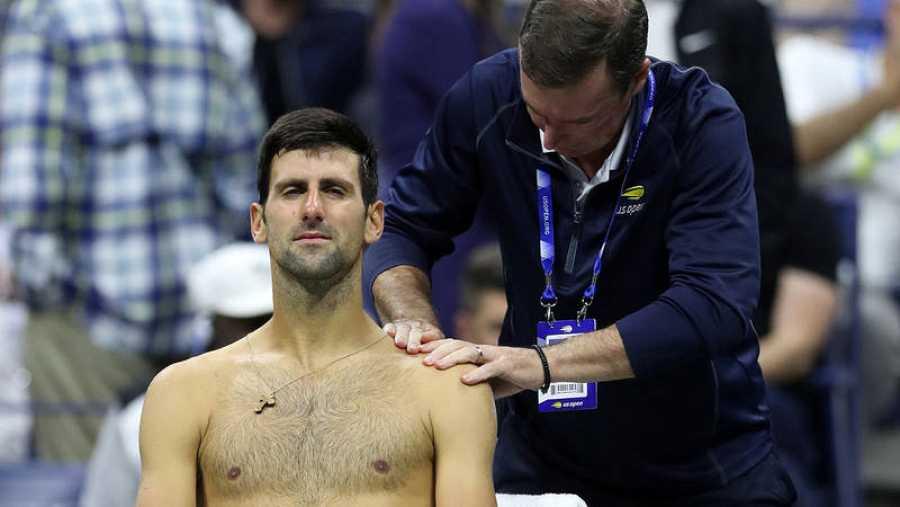 Djokovic es atendido de su hombro izquierdo durante su encuentro ante Wawrinka