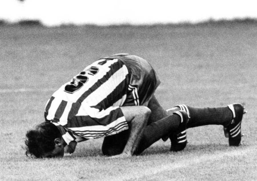 'Quini' besando el césped de El Molinón con la camiseta del Sporting.