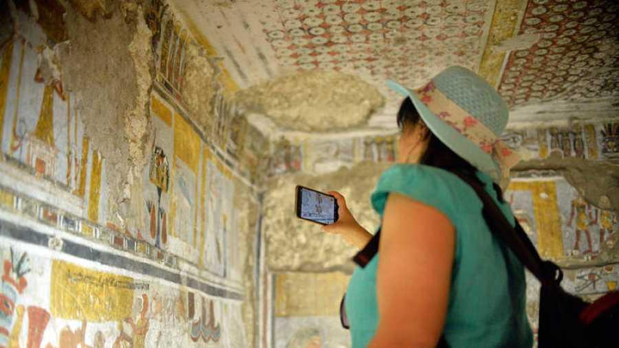 Una mujer saca una foto dentro de una de las tumbas inauguradas en Luxor
