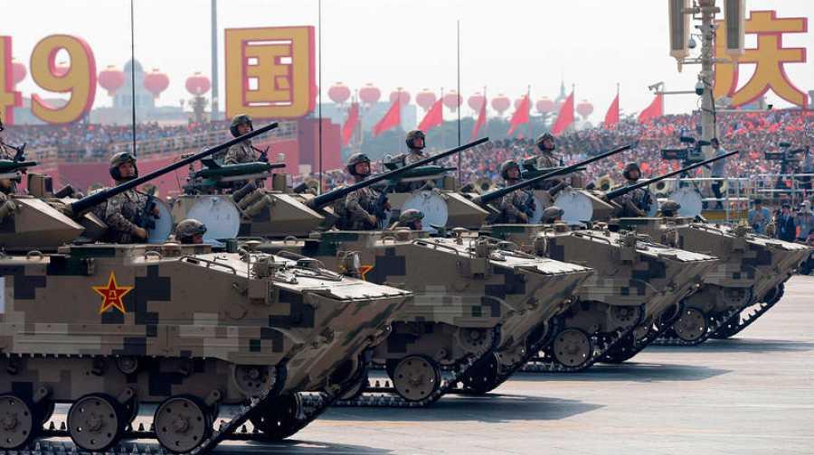 Soldados chinos a bordo de vehículos militares cruzan la plaza de Tiananmen de Pekín.