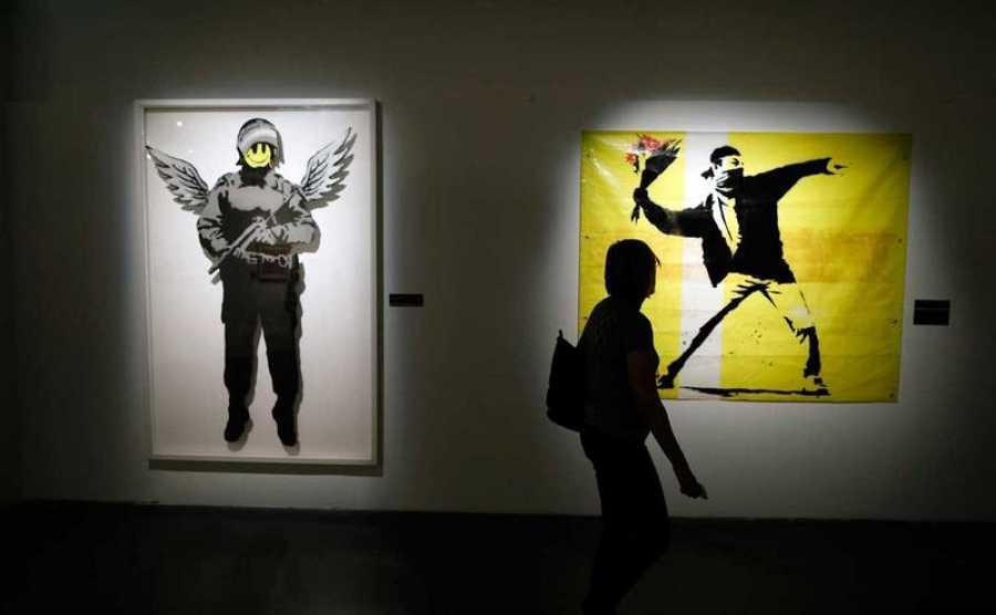 Una mujer observa las obras del artista británico Banksy durante la exposición 'El Arte de Banksy' en Herzliya, cerca de Tel Aviv, Israel, en abril de 2017