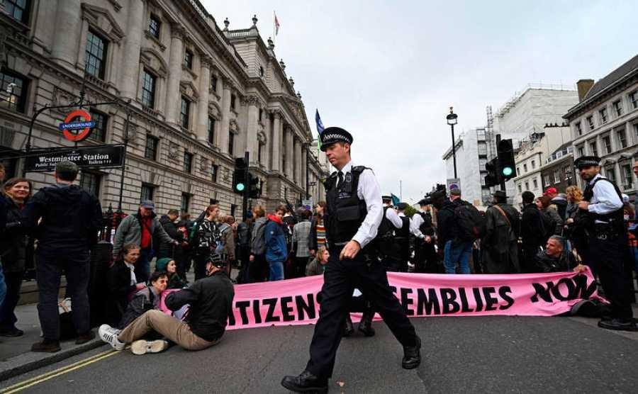 Oficiales de policía británicos hablan con varios activistas del cambio climático del grupo Extinction Rebellion mientras bloquean el cruce de las calles Whitehall y Parliament Square en el centro de Londres